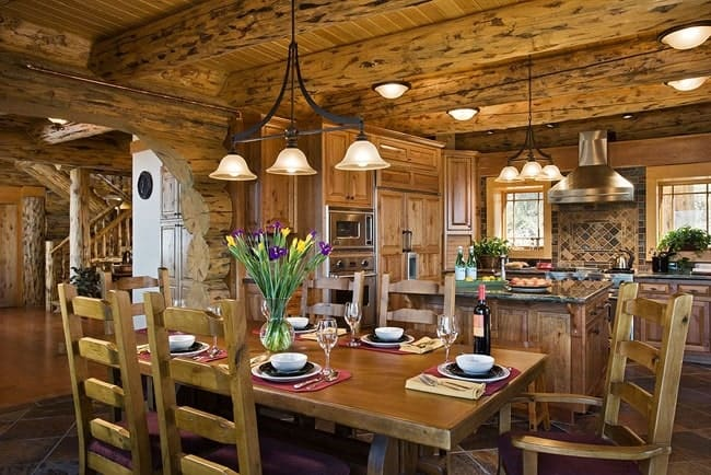 This is an informal dining area just beside the kitchen with the same wooden ceiling with exposed wooden log beams that hang a wrought iron lighting over the wooden dining set that matches the wooden tone of the ceiling and walls.
