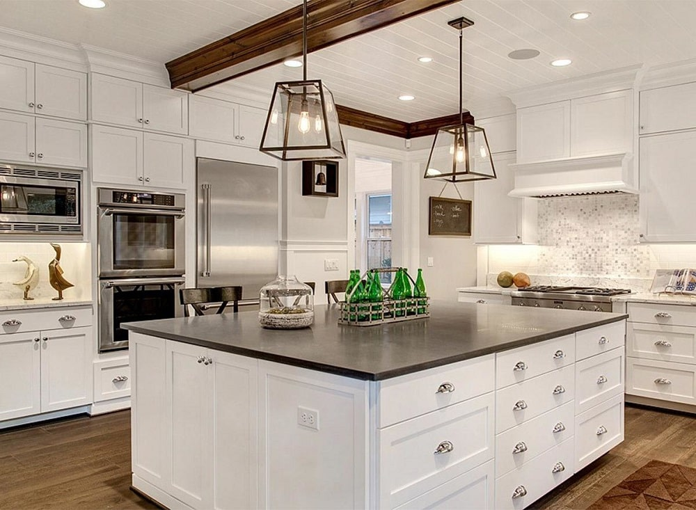 The kitchen has a large white kitchen island contrasted by the black countertop with a couple of lantern pendant lights from the beamed ceiling.