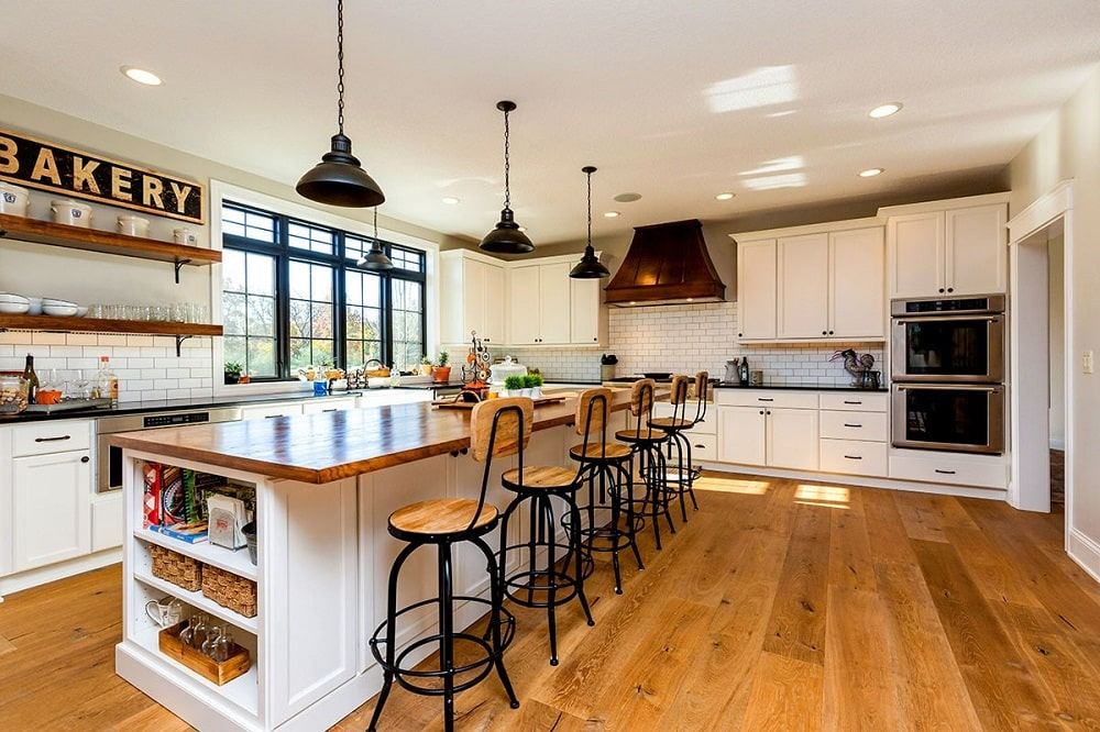 This is the large Farmhouse-style kitchen with a large kitchen island topped with pendant lights and paired with multiple stools that match the hardwood flooring and wooden countertop.