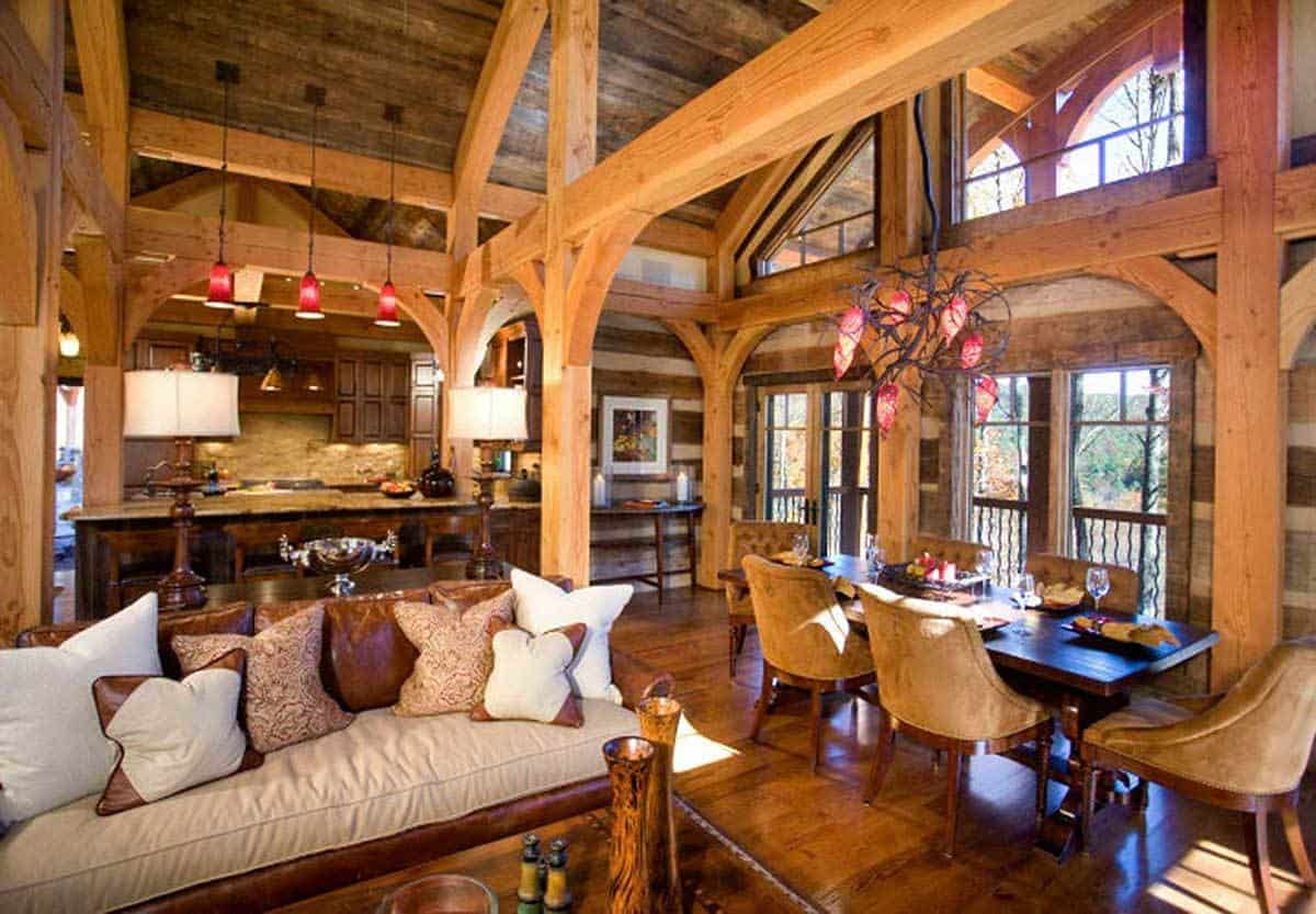 This informal dining area is a part of a great room that also houses the living room and kitchen under its tall arched wooden ceiling with exposed wooden beams and pillars. The dark wooden dining set is a nice match for the dark hardwood flooring topped with a decorative chandelier that looks like flowers in branches.