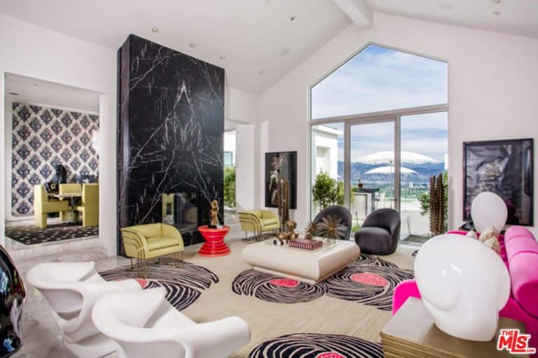 Fabulous living room showcases a black marble accent wall and a lovely patterned carpet. It includes a hot pink sofa paired with a sleek coffee table and armchairs.