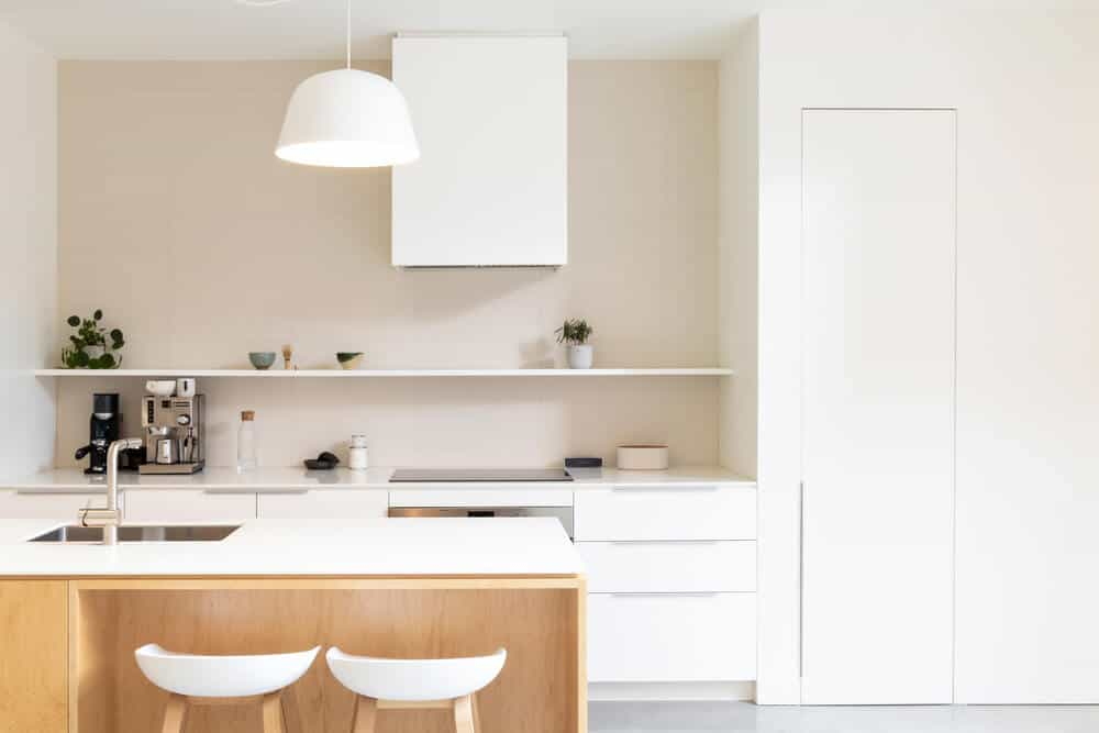 This is a close look at the kitchen with bright white elements to its kitchen island, cabinetry and even the vent hood above the cooking area on the far wall with a floating shelf above.