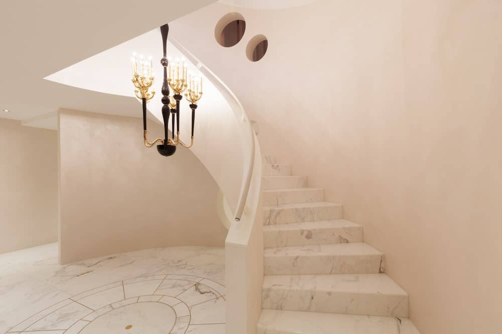 The white foyer boasts a marble flooring that matches with the stairwell steps fixed to the white wall and illuminated by a vintage candle chandelier.