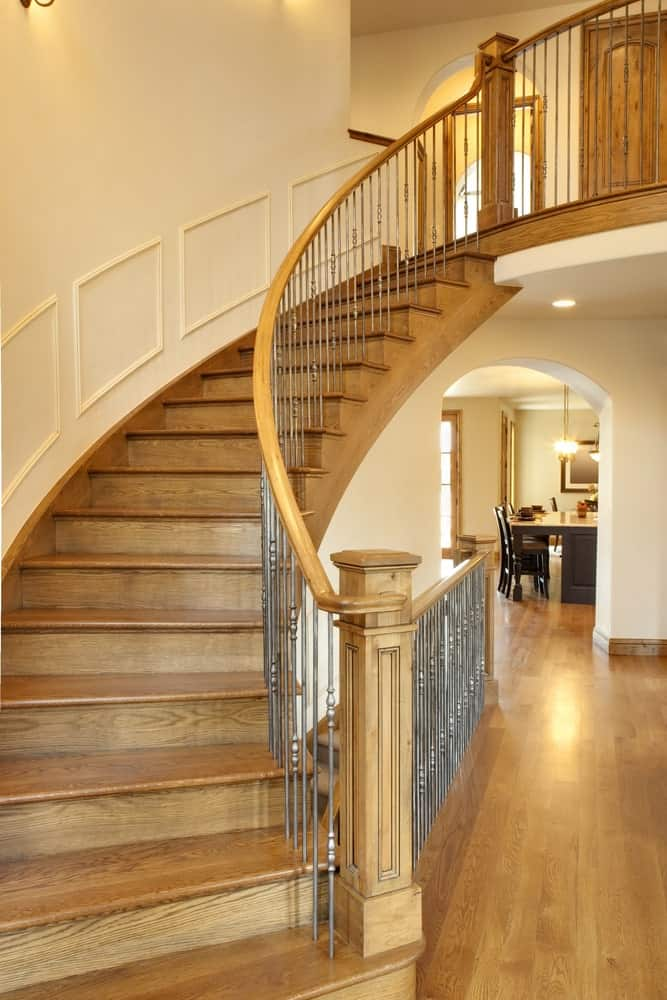A wooden curved staircase with metal spindles lined with light wood handrail and newel post. It is fixed on a cream wall styled with wainscoting.