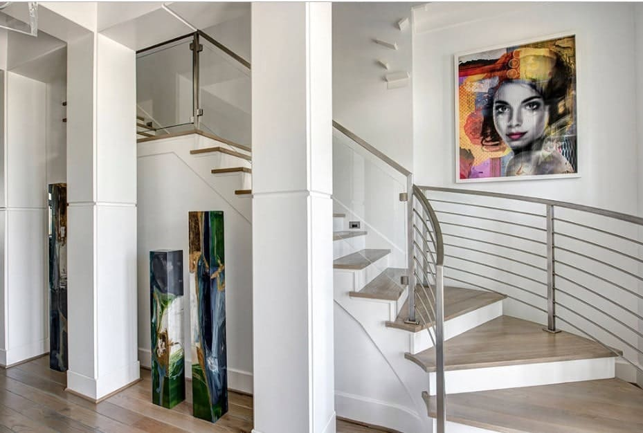 White foyer decorated with colorful pillars against the columns and a lovely portrait mounted above the curved staircase with a combination of metal and glass railings.