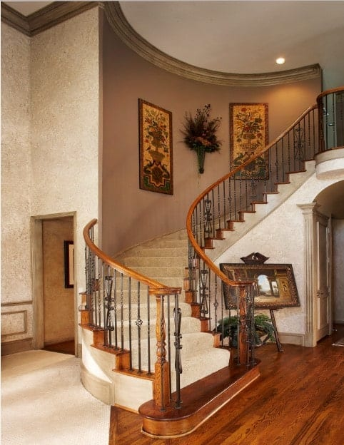 Tuscan style staircase with beige concrete steps and wrought iron railings fixed to the gray wall designed with floral artworks and decor.