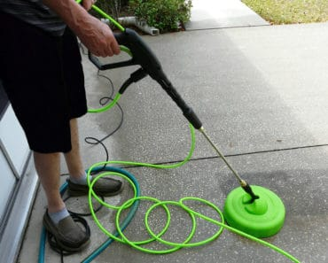 Cleaning driveway with pressure washer surface cleaner