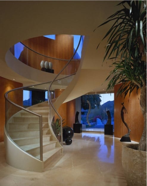 Contemporary curved staircase surrounded with modern sculptures and indoor plants. It has marble steps with glass balustrades topped with stainless steel handrails.