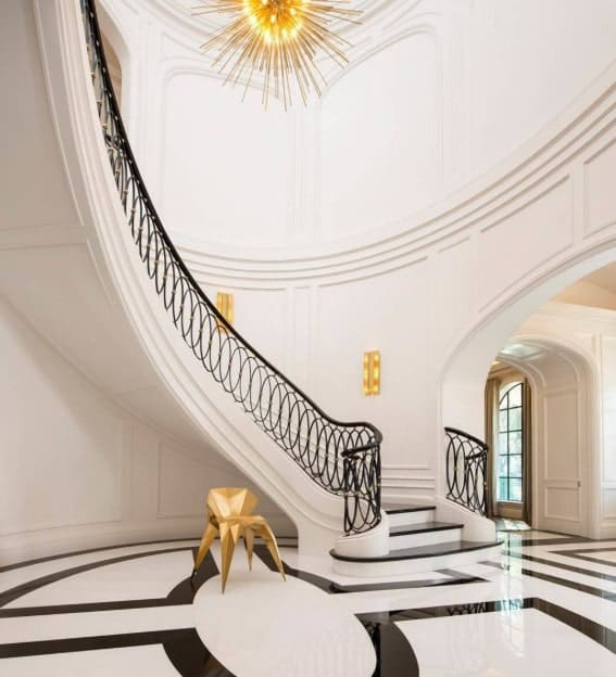 Deluxe white foyer showcases a gold geometrical chair beside a curved staircase fitted with black ornate balustrade illuminated by wall sconces and a sunburst chandelier.