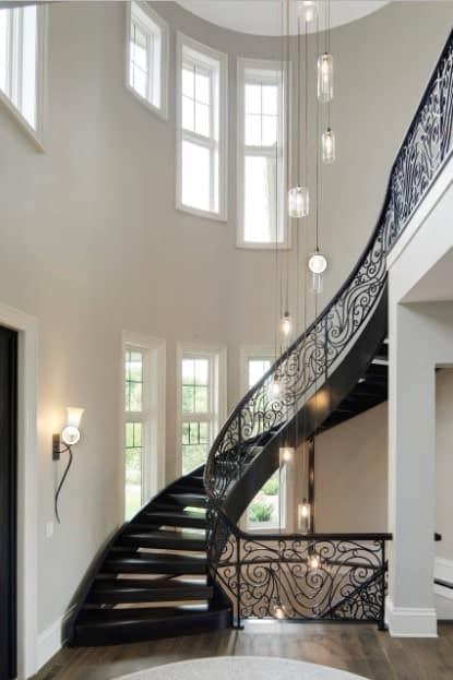 Black wooden staircase styled with an ornate balustrade and illuminated by a wall sconce and industrial chandelier.