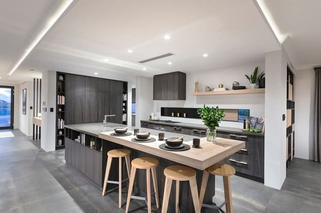 Asian style kitchen illuminated by recessed and strip lights fixed on the drop ceiling. It has an island bar lined with wooden bar stools and topped with gray marble and an L-shaped wood counter.