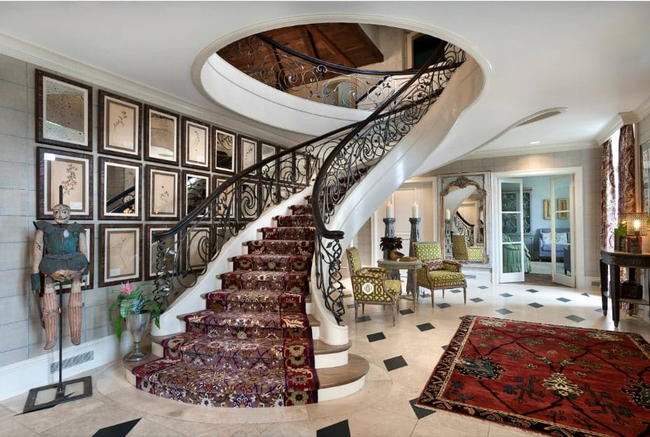 Eclectic foyer designed with gallery frames mounted on the gray wall beside a curved staircase framed with ornate wrought iron railings and dressed in a patterned stair runner.