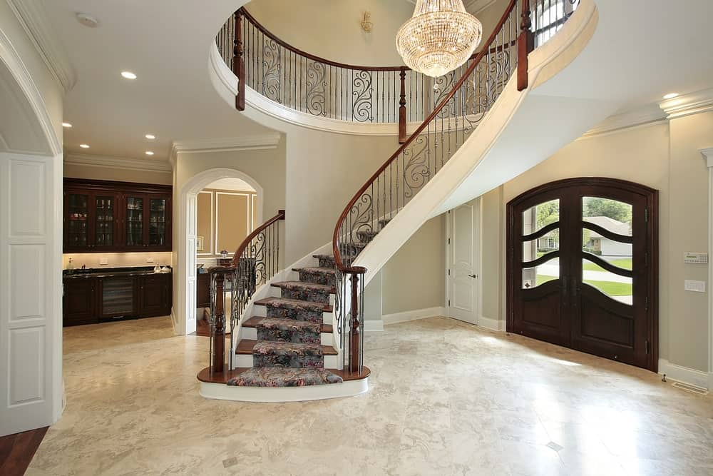 A dark wood front door with glass panels opens to a spacious foyer with marble flooring and curved staircase wrapped in a printed carpet.