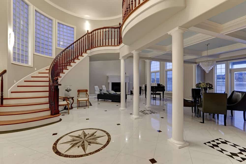 Elegant foyer showcases a coffered ceiling and white columns along with a curved staircase fitted with redwood balustrade.
