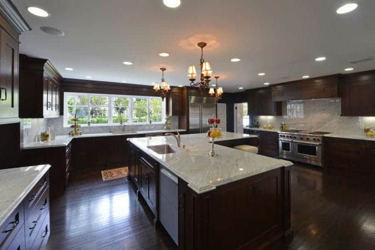 The dark wooden tones of the hardwood flooring and the wooden cabinets and drawers of the L-shaped island and surrounding peninsulas are brightened by the abundance of natural lights coming in from the row of windows as well as the pair of chandeliers.