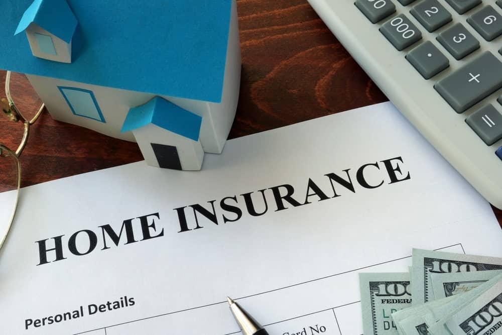 Home insurance form with model house, calculator, glasses, pen, and dollars on the side.