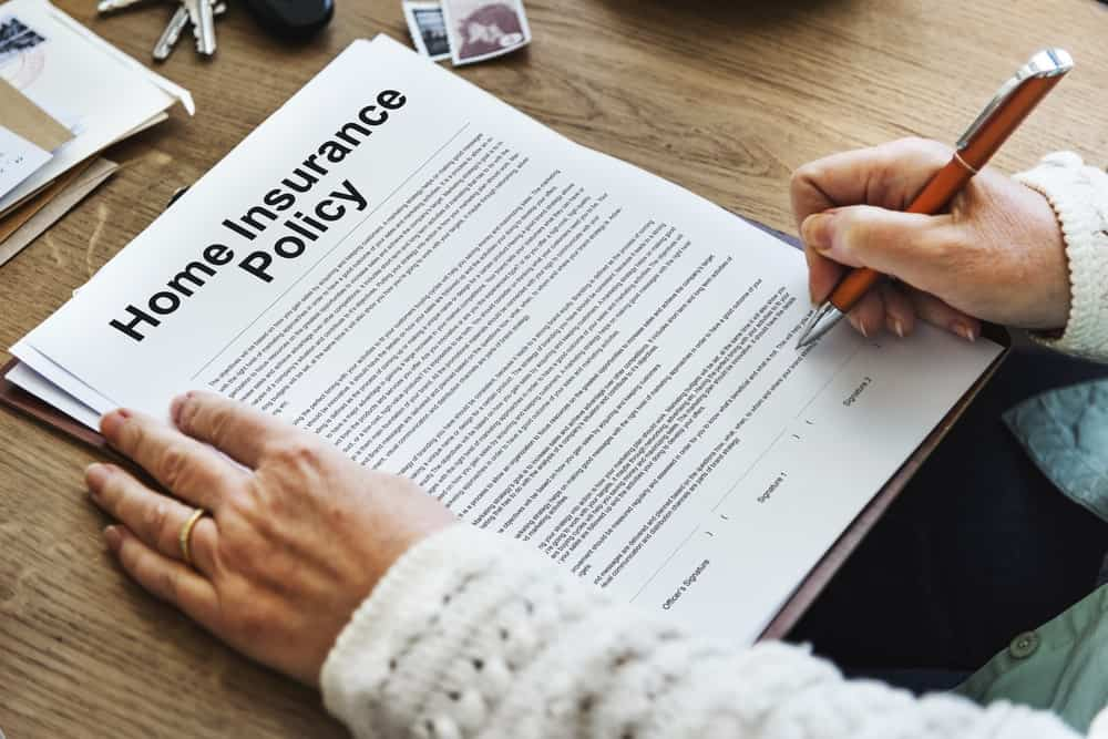 Person signing a home insurance policy form.