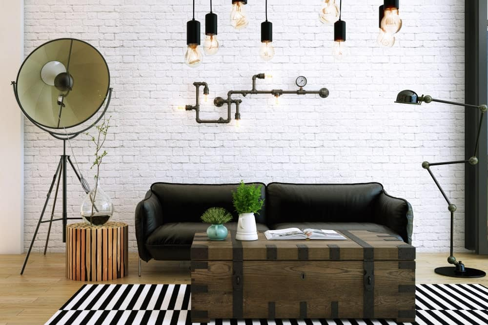 Living room filled with various lighting fixtures such as bulb pendants, black dome floor lamp, tripod floor lamp and pipe lights mounted on the white brick wall.