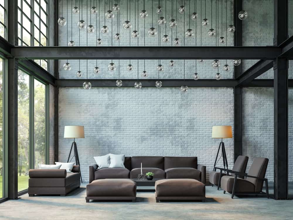 This living room is designed with bubble glass pendant lights that hung from the high ceiling. It has a stylish brick wall framed with metal beams.