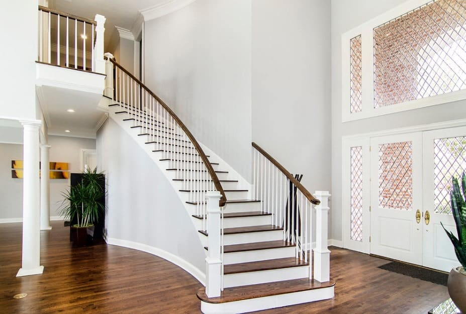 Transitional staircase fitted with white spindles along with wooden handrails and treads that complements with the foyer's hardwood flooring.