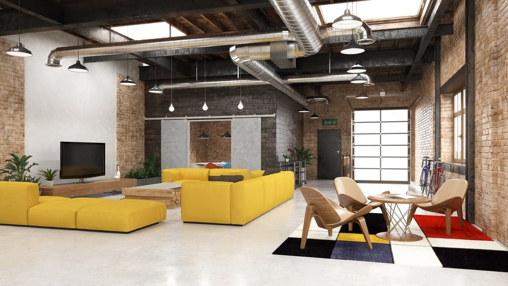 Spacious living room boasts two sitting areas bursting with colors. It has a wood beam ceiling lined with industrial metal pipes and pendant lights.