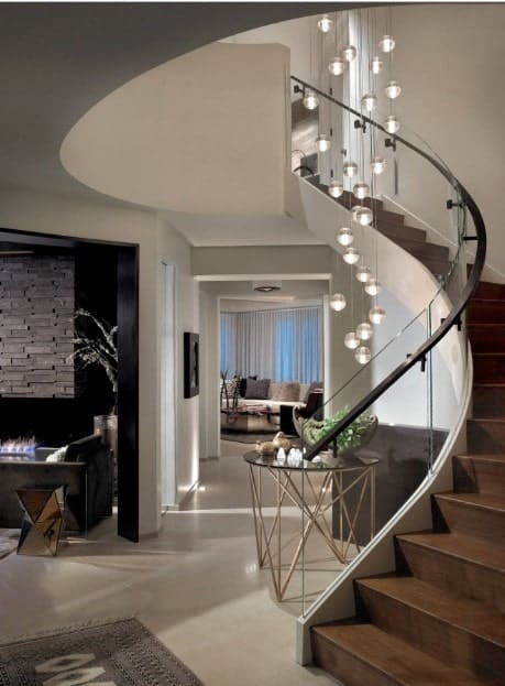 Modern foyer features a wooden staircase with white stringer and glass balustrade lined with a black steel handrail. It is lighted by a cascading glass bubble chandelier.