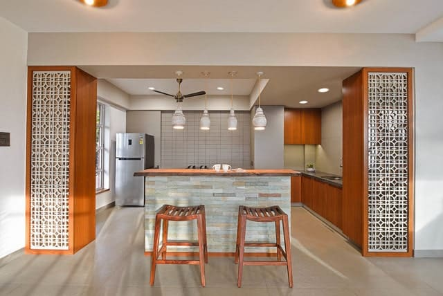 Charming kitchen features a brick breakfast island with wooden counter chairs and illuminated by pendant lights. It has rich wooden storage on both sides framed with white ornate panels.