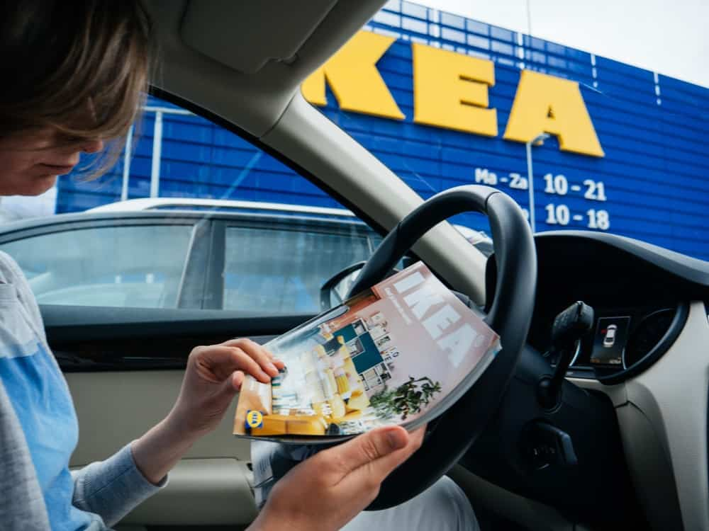 A Woman inside the Car with IKEA Catalog