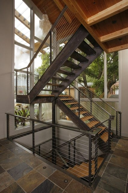 Industrial staircase without riser fitted with wood treads and black metal handrails on an open floor.