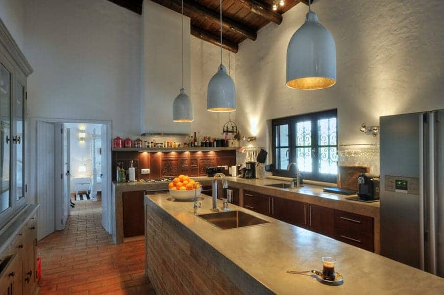 The dark wooden ceiling has exposed wooden log beams that matches the cabinets of the L-shaped peninsula. This hue works well with the earthy terracotta tiles of the flooring as well as the gray waterfall countertops of both the island and peninsula.