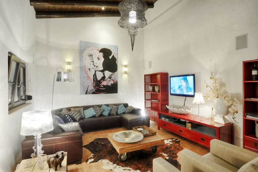 Spanish living room with a rustic feel. It is decorated with a wall art piece lighted by wall sconces along with an industrial chandelier. Red tv stand and shelves stand out from this room.