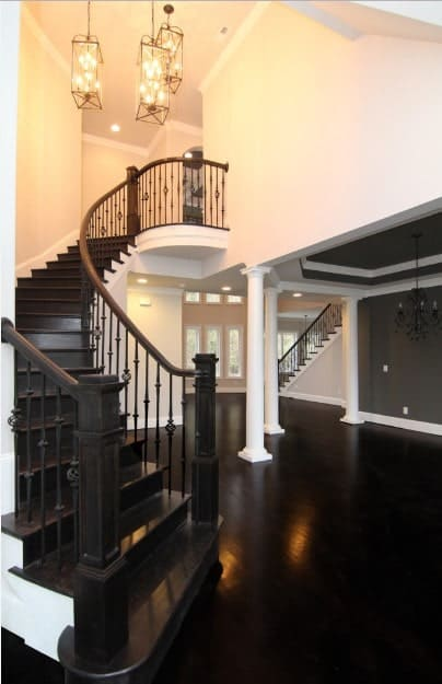 Fancy caged chandeliers hung over an ebony wood staircase with ornate black steel spindles lined with wooden handrails and newel posts.