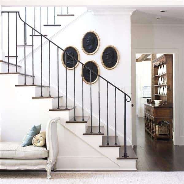 Traditional staircase with hand-wrought railing and dark wood treads accented by black oval wall decors. Beneath it is an elegant chaise lounge over a white carpet.