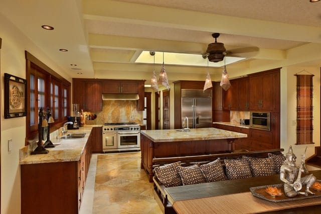 An open kitchen showcases natural wood cabinetry and marble flooring that complements with the countertops and backsplash tile creating a unified look.