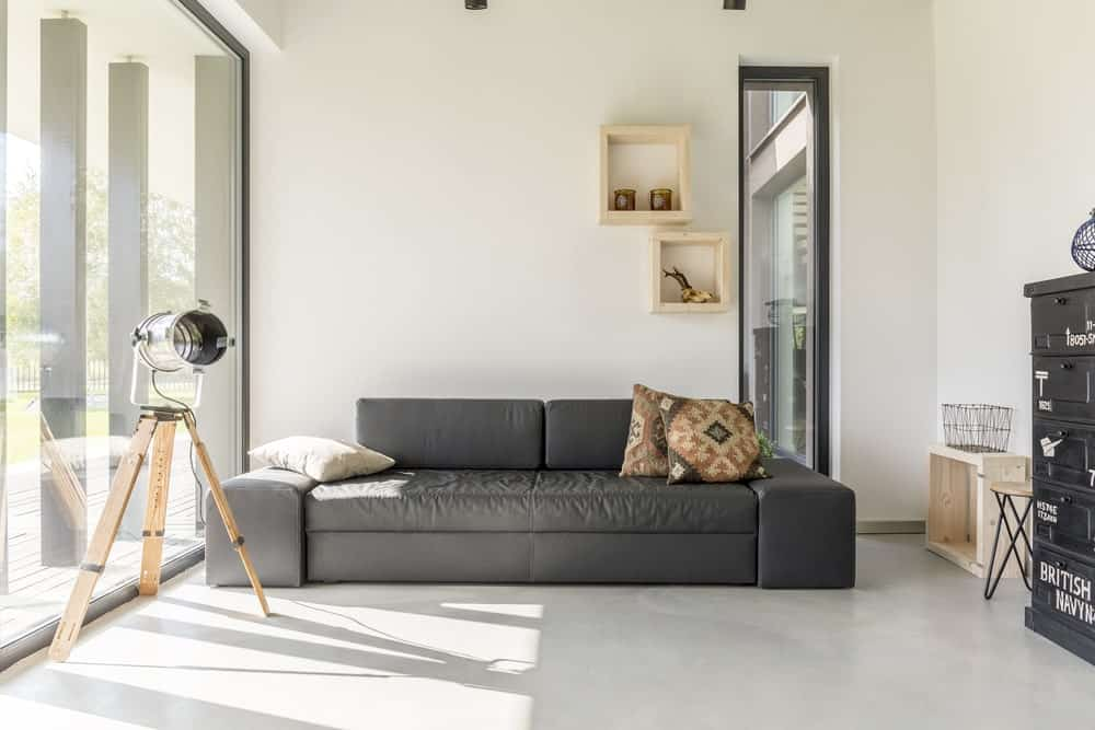 Simple living room offers light wood floating shelves mounted above a gray couch with patterned throw pillows. It is lighted by a tripod floor lamp and natural light that flows through the glass window.