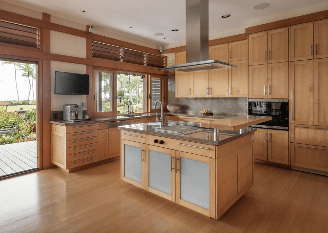 A stainless steel vent hood stands over a wooden kitchen island topped with gray marble and a raised light wood counter in this wood themed kitchen.