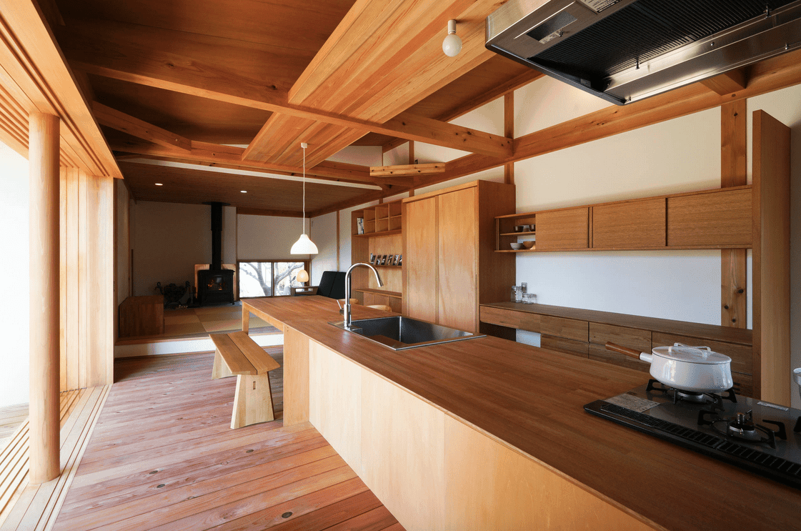 An all wood kitchen boasts a lengthy island bar with wooden bench and fitted with chrome faucet and sink.