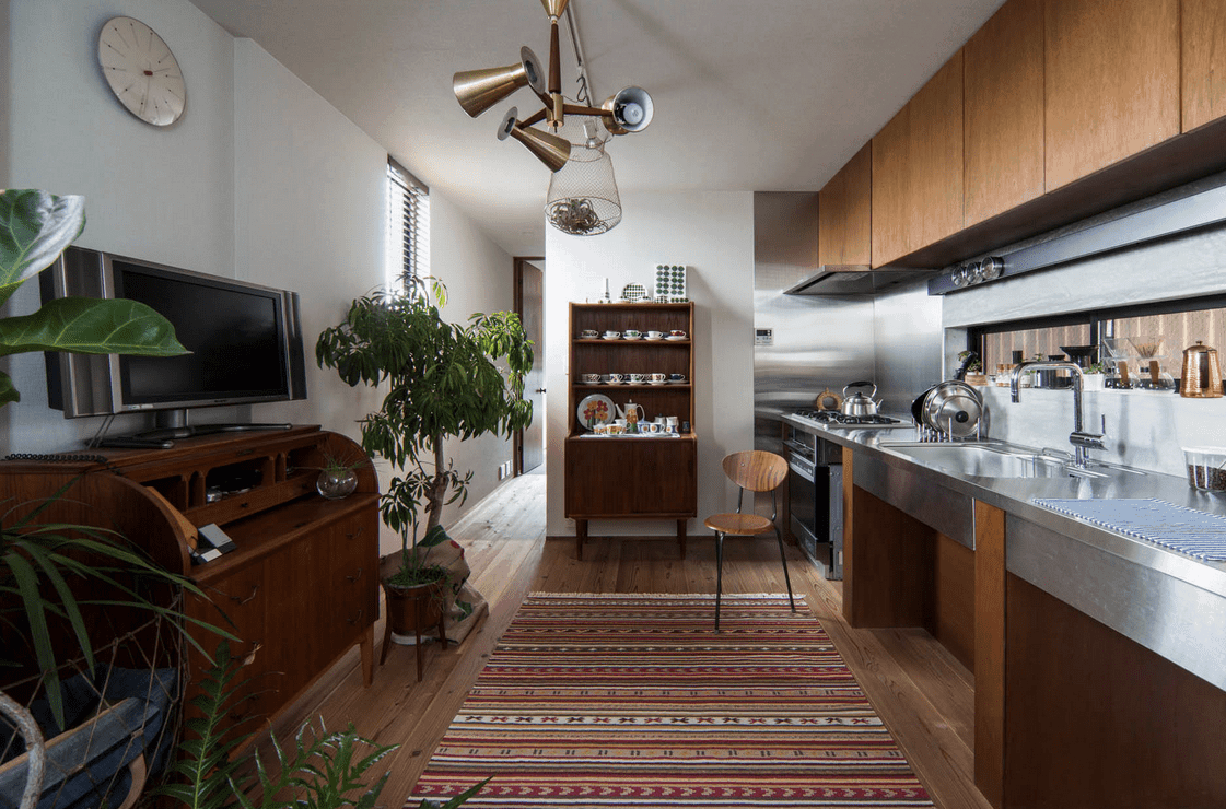 A unique pendant light hangs over a patterned rug that lays on the hardwood flooring illuminating this cozy kitchen. It has wooden cabinetry and stainless steel countertop.