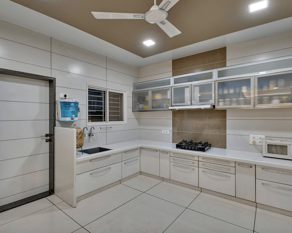 White kitchen contrasted by a taupe ceiling and accent backsplash tile. It has frosted glass front upper cabinets and white wooden lower cabinetry.