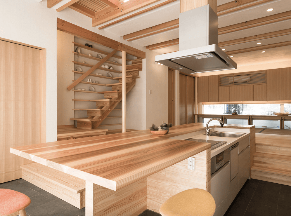 Asian style kitchen features a two-tier breakfast island fitted with a cooktop and sink. It has floating shelves next to the staircase decorated with white dinnerware.