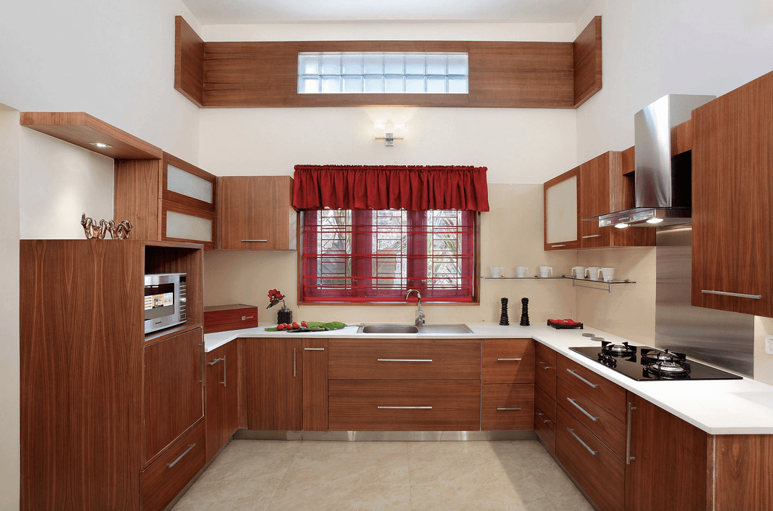 This kitchen offers redwood cabinetry and glass windows covered with red valence and sheer roman shade. It has white countertop fitted with a sink and cooktop.