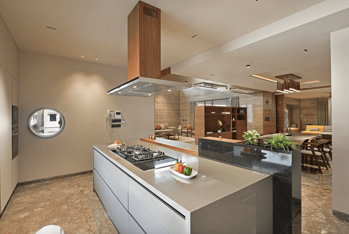 A wooden range hood stands over the gray breakfast island fitted with a built-in cooktop in this open kitchen. It has marble flooring and a round glass window.
