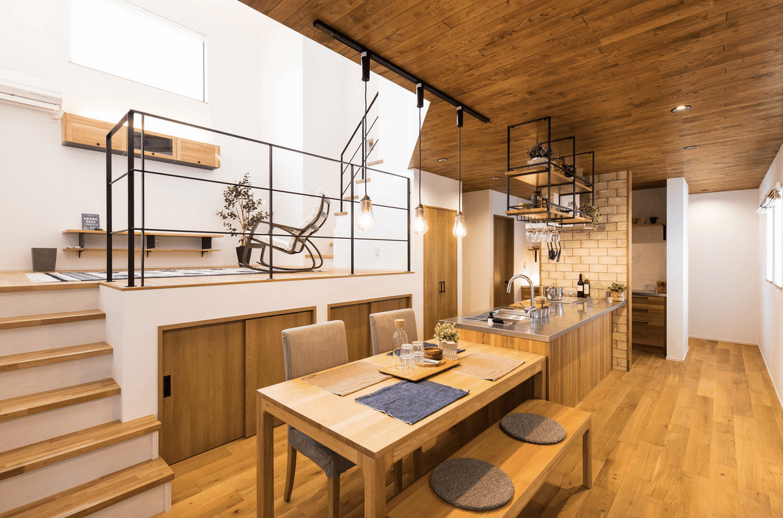Warm kitchen boasts a wooden peninsula topped with stainless steel counter and lined with an extended breakfast bar paired with upholstered chairs and a wooden bench.