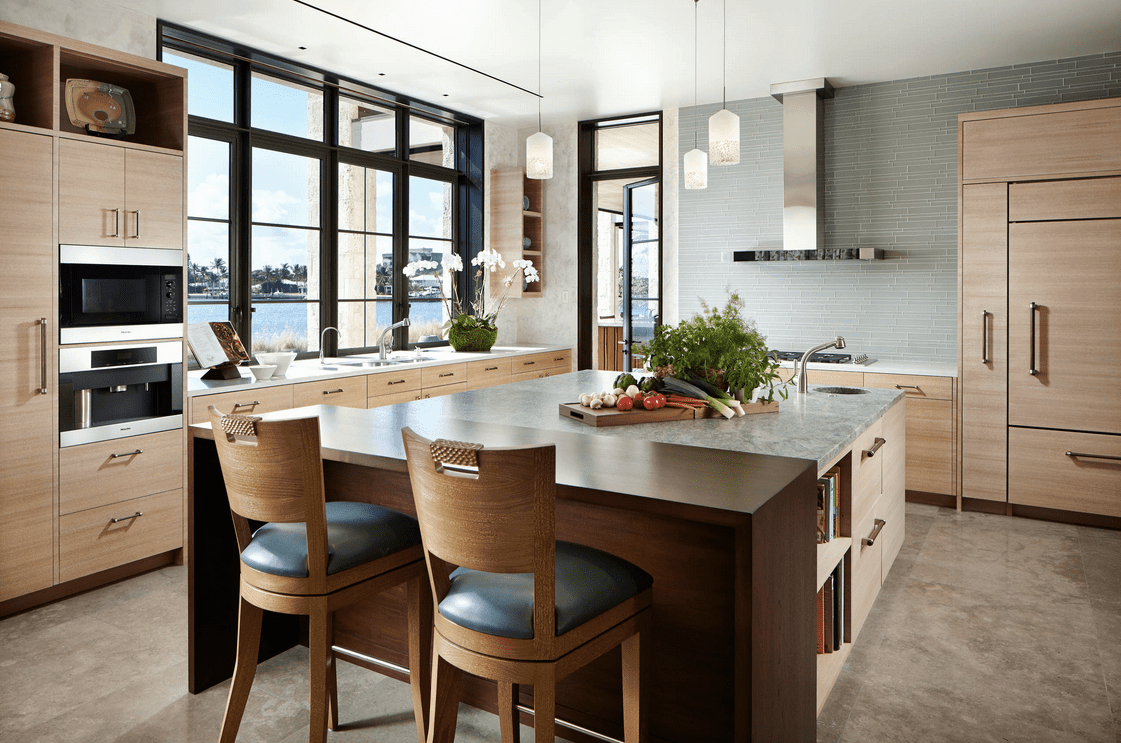 Fresh kitchen boasts black paneled glass windows and a breakfast island lighted by fancy pendants. It includes a sleek range hood fixed to the gray brick backsplash.
