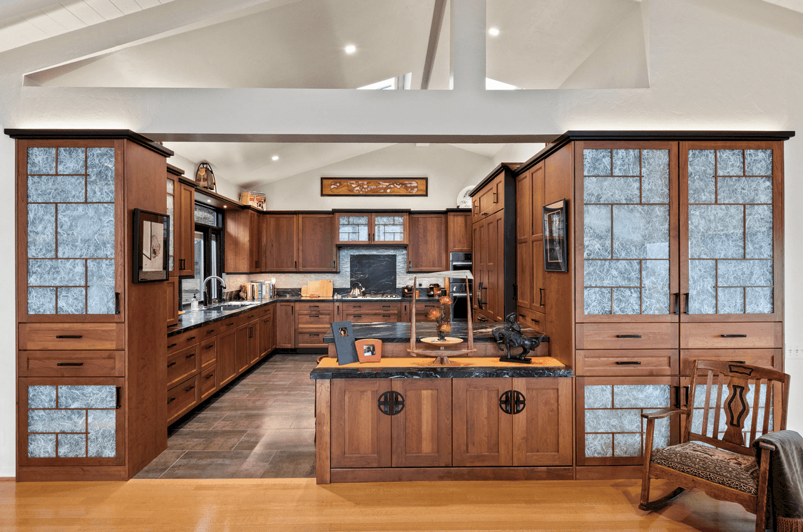 Japanese inspired kitchen with cherry wood cabinetry and limestone flooring. It has a two-tier peninsula topped with black marble counters and styled with lovely decors.