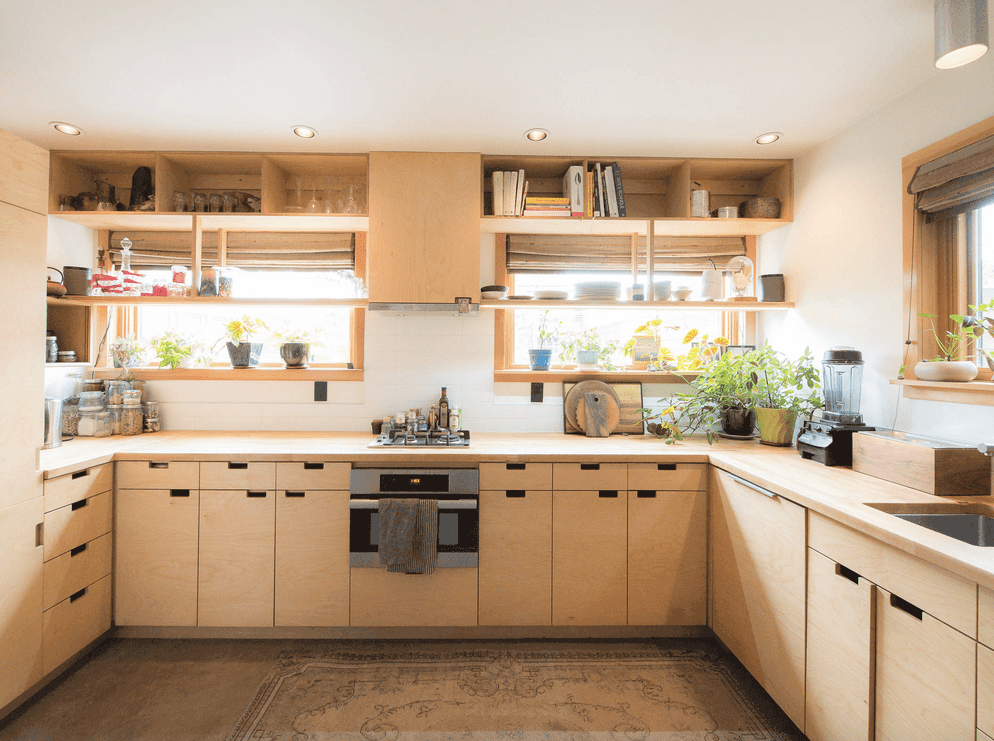 An airy kitchen offers light wood stained cabinetry with open shelving. It is accented with potted plants that add a refreshing ambiance to the room.