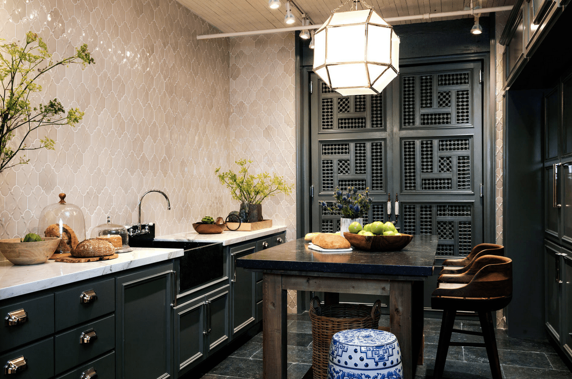 Fabulous kitchen designed with a beige decorative tile backsplash and an ornate black door that complements with the cabinetry. It includes a wooden kitchen island lighted by an oversized pendant and track lights mounted on the white wood plank ceiling.