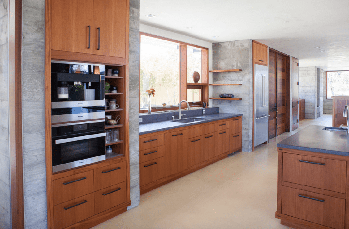 Expansive kitchen showcases wood cabinetry and gray countertops. It has floating shelves mounted on the concrete wall adjacent to the glass window.
