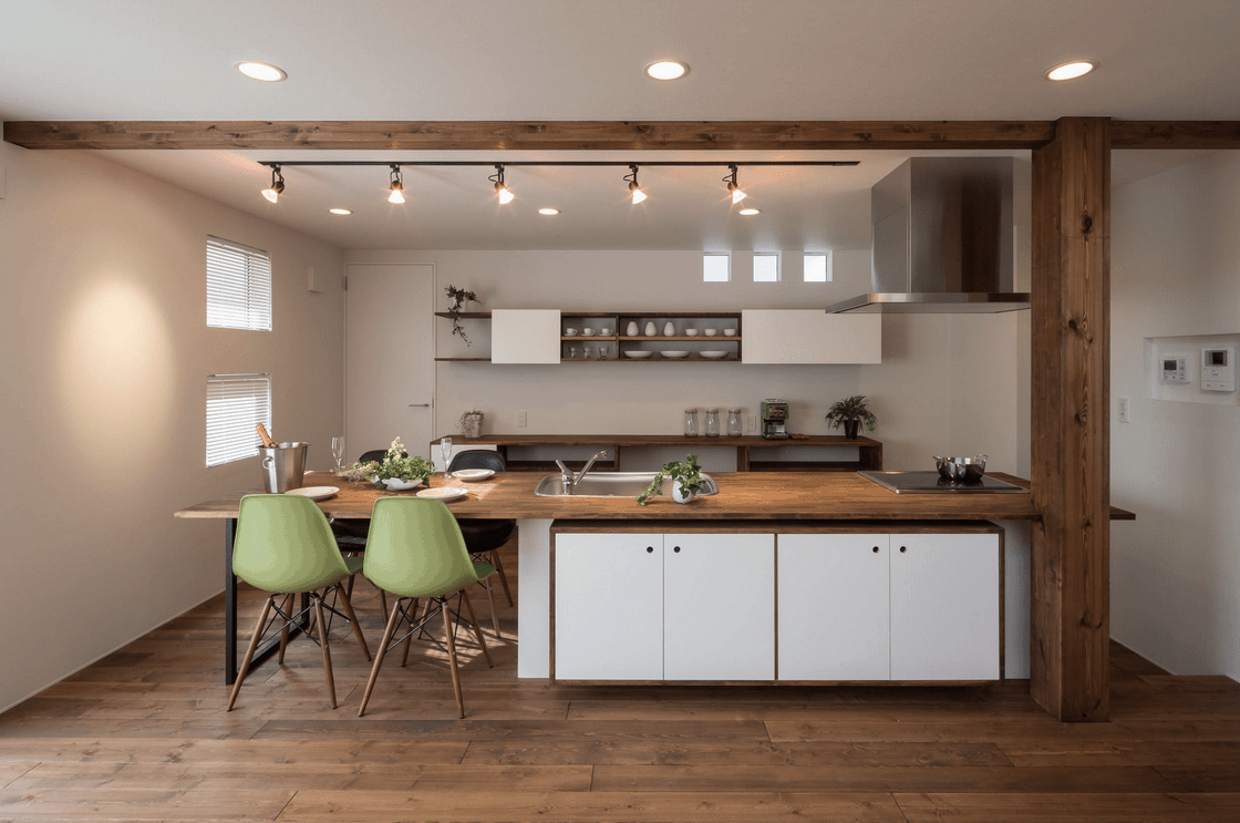Fresh kitchen framed with wood beams that complement with the wood plank flooring and counters. It has a white peninsula paired with black and light green stools.