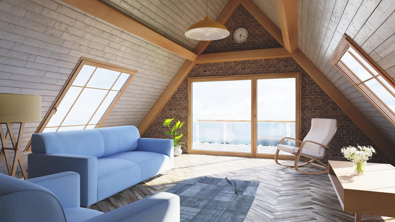 Loft living room offers adjacent soft blue couch and armchair over herringbone wood flooring. It has a wood plank and red brick cathedral ceiling fitted with wooden framed windows.